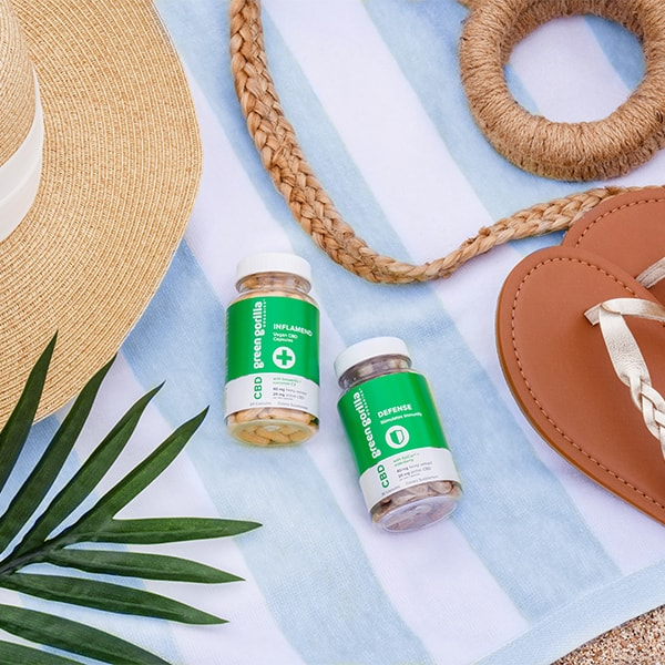 Two jars of CBD capsules on a beach blanket with sunhat and sandals.