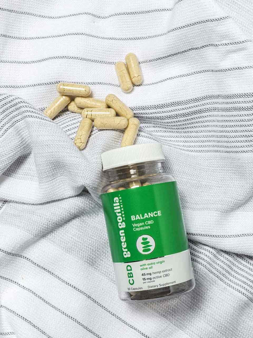 Loose CBD capsules and bottle of Green Gorilla CBD Balance capsules