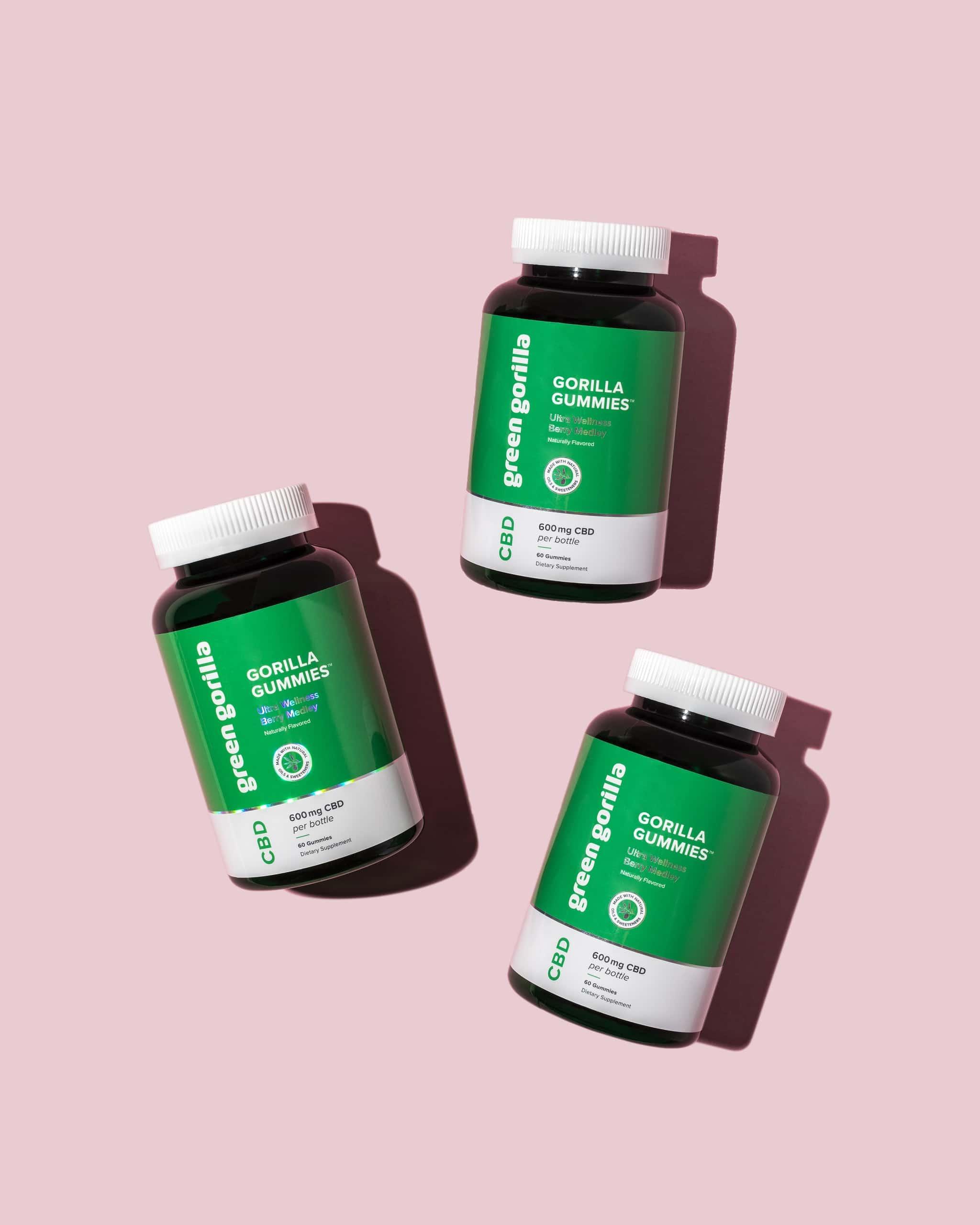 three bottles of Green Gorilla™ hemp CBD gummies on pink background