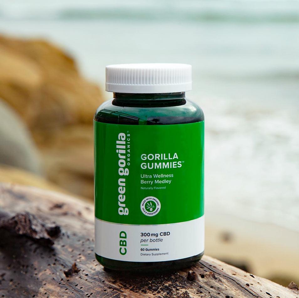 A jar of Green Gorilla™ gummies on a cliff overlooking the beach.