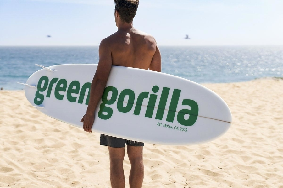 """Man in swimsuit holding a surfboard that says """"Green Gorilla™."""""""