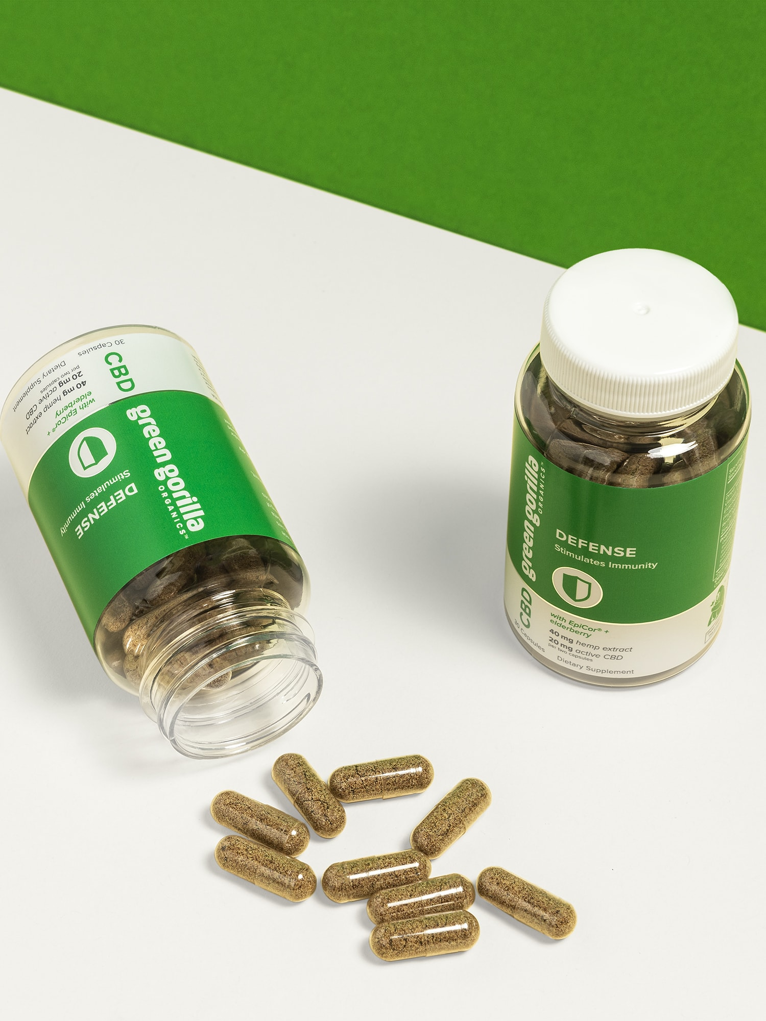 One open and one closed jar of CBD defense capsules with loose capsules