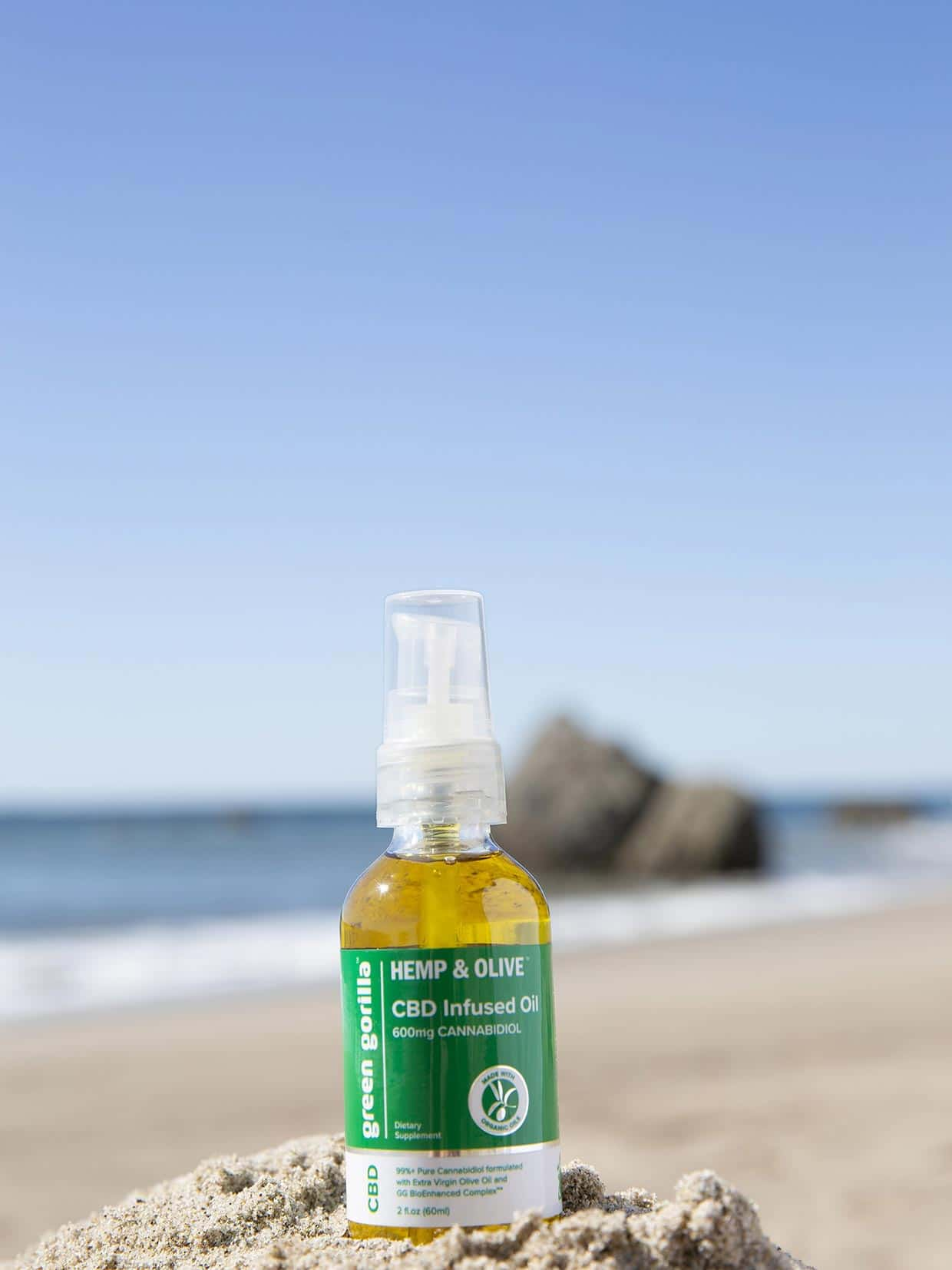 A bottle of 600mg Green Gorilla™ pure CBD oil on a rock at the beach.