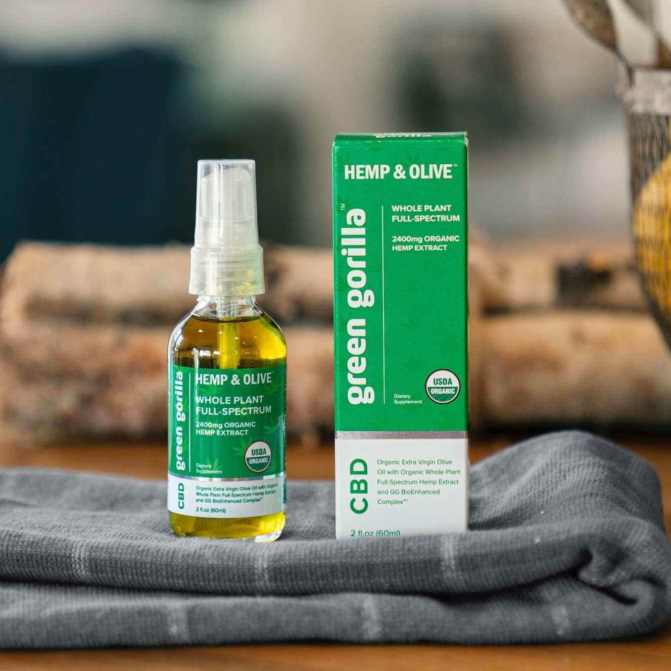 Hemp & Olive CBD oil sitting on a towel next to its box.