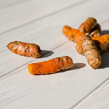 Raw turmeric on a wooden surface.