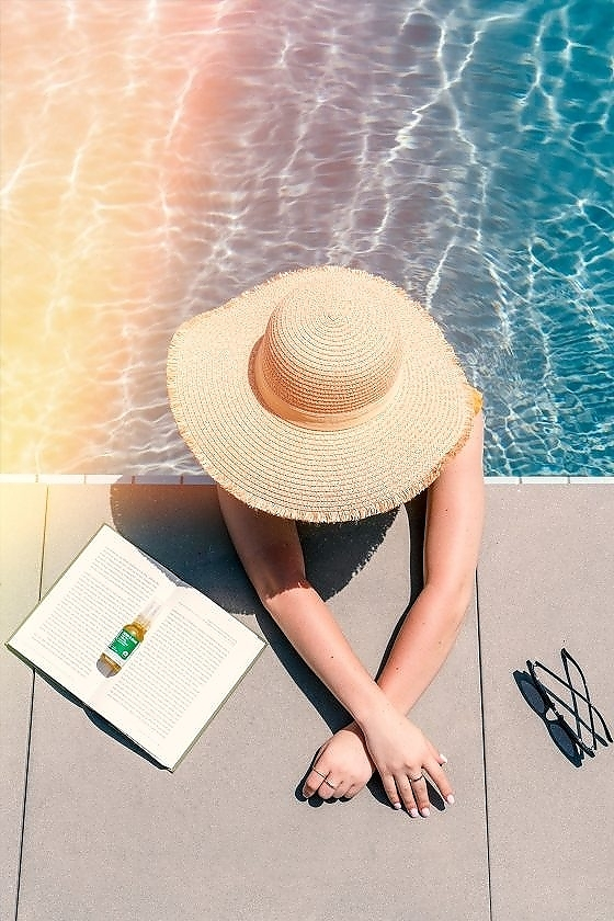 A top view of a woman in sunhat at the swimming pool with a book, sunglasses, and Green Gorilla™ CBD oil.